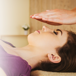 hands over a womans face performing reiki